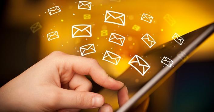 Bild: Finger auf Tablett mit viele E-Mail-Symoblen / mit Google Analytics Newsletter trocken